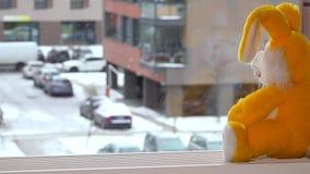 Conejito amarillo del juguete que se sienta en travesaño de la ventana El caer de los copos de nieve almacen de metraje de vídeo