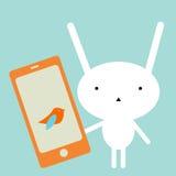 Conejito con un smartphone Fotografía de archivo