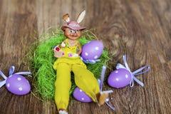 Conejito de cerámica amarillo de pascua con los huevos púrpuras foto de archivo libre de regalías