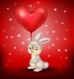 Conejito de la historieta que sostiene los globos rojos del corazón Imagenes de archivo