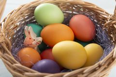 Conejito de madera en a con la cesta con los huevos de Pascua coloridos fotos de archivo libres de regalías