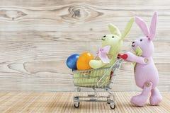 Conejito de pascua con el carro de la compra y los huevos de Pascua Fotos de archivo