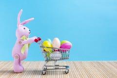 Conejito de pascua con el carro de la compra y los huevos coloridos Imagenes de archivo