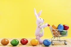 Conejito de pascua con el carro de la compra y los huevos de Pascua coloridos Fotografía de archivo libre de regalías