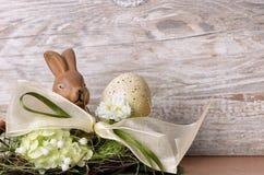 Conejito de pascua con el huevo de Pascua en la jerarquía Fotos de archivo libres de regalías
