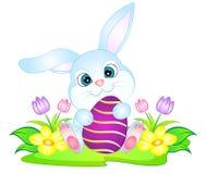 Conejito de pascua con los huevos y las flores