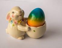 Conejito de pascua con una cesta con el huevo colorido pintado Fotos de archivo