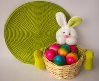 Conejito de pascua con una cesta con los huevos coloridos pintados Fotos de archivo libres de regalías
