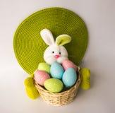 Conejito de pascua con una cesta con los huevos coloridos pintados Imagen de archivo