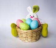 Conejito de pascua con una cesta con los huevos coloridos pintados Foto de archivo