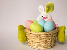 Conejito de pascua con una cesta con los huevos coloridos pintados Imagen de archivo libre de regalías