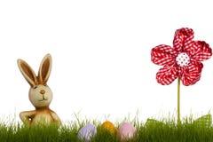 Conejito de pascua detrás de la hierba con la flor de la pañería y Imagen de archivo libre de regalías