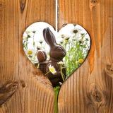 Conejito de pascua detrás de un corazón Imágenes de archivo libres de regalías