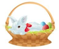Conejito de pascua en cesta de mimbre El conejito de pascua lindo que se sienta en cesta con color eggs Foto de archivo
