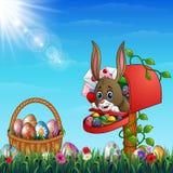 Conejito de pascua hacia fuera del buzón con la cesta de Pascua por completo de huevos de Pascua adornados en un campo de hierba ilustración del vector
