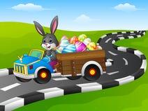 Conejito de pascua que conduce un coche que lleva los huevos de Pascua en el camino stock de ilustración
