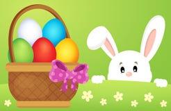 Conejito de pascua que está al acecho por la cesta con los huevos Foto de archivo
