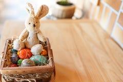 Conejito de pascua y huevos coloridos en la cesta en el fondo de madera Lugar para el texto Tarjeta feliz de la celebración de Pa imagen de archivo libre de regalías
