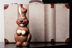 Conejito del chocolate de Pascua, con una maleta Foto de archivo libre de regalías
