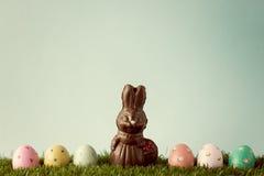 Conejito del chocolate del vintage con los huevos de Pascua sobre hierba Fotografía de archivo libre de regalías