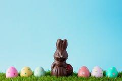 Conejito del chocolate del vintage con los huevos de Pascua sobre hierba Foto de archivo libre de regalías