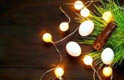Conejito del chocolate y huevos de blancos en la textura orgánica de la hierba verde en fondo de madera Composición del día de fi imagen de archivo