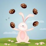Conejito divertido con los huevos de chocolate para Pascua feliz Imágenes de archivo libres de regalías