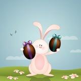 Conejito divertido con los huevos de chocolate para Pascua feliz Foto de archivo