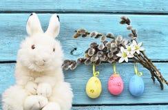 Conejito divertido de Pascua en fondo y los huevos de Pascua de madera Fondo de Pascua Foto de archivo