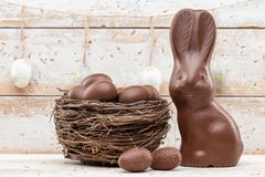 Conejito, huevos y dulces de pascua del chocolate en fondo rústico imagenes de archivo