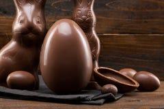 Conejito, huevos y dulces de pascua del chocolate en fondo rústico fotos de archivo libres de regalías