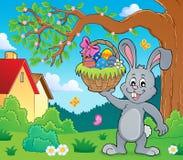 Conejito que lleva a cabo el tema 2 de la cesta de Pascua stock de ilustración