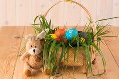 Conejito y cesta de pascua con los huevos de Pascua pintados Imagenes de archivo