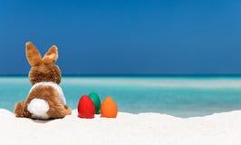 Conejito y huevos de Pascua coloreados en una playa Fotografía de archivo
