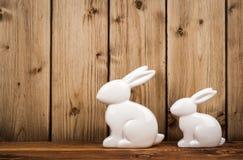 Conejitos de la decoración de Pascua con los huevos de Pascua en la jerarquía en el fondo de madera Imágenes de archivo libres de regalías