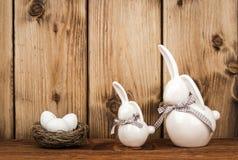 Conejitos de la decoración de Pascua con los huevos de Pascua en la jerarquía en el fondo de madera Fotografía de archivo libre de regalías