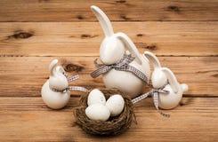 Conejitos de la decoración de Pascua con los huevos de Pascua en la jerarquía en el fondo de madera Fotos de archivo