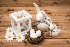 Conejitos de la decoración de Pascua con los huevos de Pascua en la jerarquía en el fondo de madera Foto de archivo
