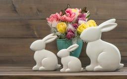 Conejitos de pascua con las flores de los tulipanes Fotos de archivo