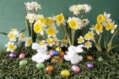 Conejitos de pascua con las flores y la cesta Fotos de archivo libres de regalías