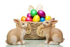 Conejitos de pascua que se sientan delante de los huevos de Pascua Fotos de archivo libres de regalías