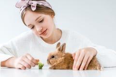 Conejo de alimentación sonriente de la muchacha con bróculi en blanco Fotos de archivo libres de regalías