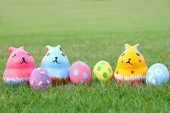Conejo de cerámica colorido tres con los huevos en hierba superior en Pascua Fotos de archivo