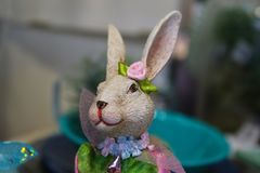 Conejo de conejito bonito de la muchacha todo cubierto hacia fuera para la primavera con las flores y las cintas contra fondo del Imagen de archivo libre de regalías