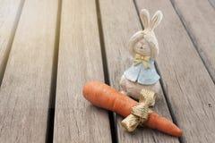 Conejo de madera con el regalo fresco de la zanahoria en piso de madera Foto de archivo libre de regalías