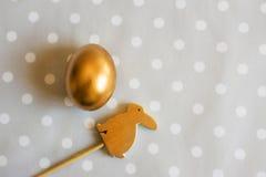 Conejo del huevo de Pascua del oro y madera adornado, arriba Foto de archivo libre de regalías