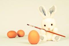 Conejo del juguete con los huevos y el cepillo de pintura Imagenes de archivo