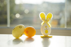 Conejo divertido del juguete con los huevos de Pascua coloridos en ventana Foto de archivo