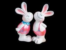 Conejo doble hecho de cerámica, aislado en fondo negro imagen de archivo