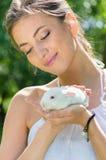 Conejo sonriente feliz joven del abarcamiento de la mujer pequeño al aire libre Imagen de archivo libre de regalías